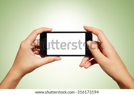 Hand holding smartphone with blank screen isolated on green background - stock photo