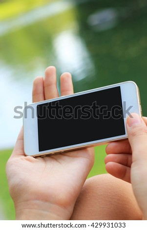 Hand holding smartphone with blank screen. selective focus.