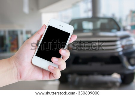 hand holding smartphone with car showroom blurred background, buying new car - stock photo