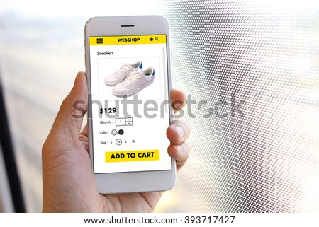 Hand holding smartphone with choose shoes on ecommerce website
