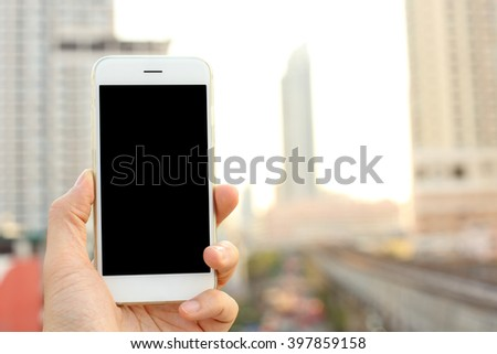 Hand holding smartphone with cityscape background