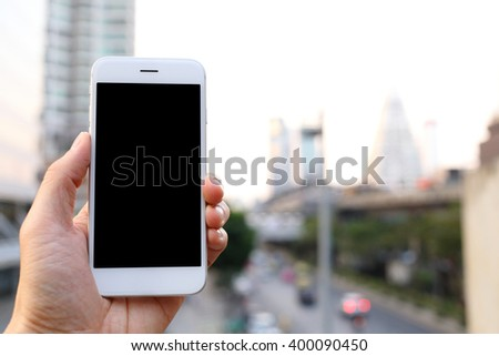 Hand holding smartphone with cityscape background - stock photo