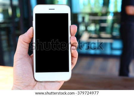 Hand holding smartphone with coffee shop background