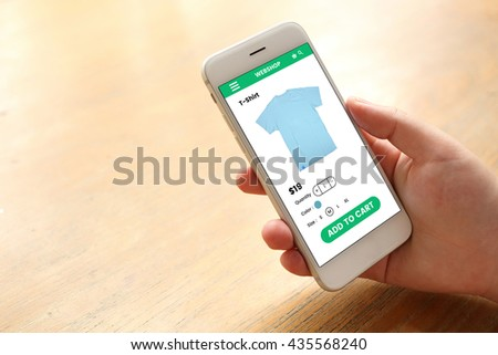 Hand holding smartphone with ecommerce screen website - stock photo