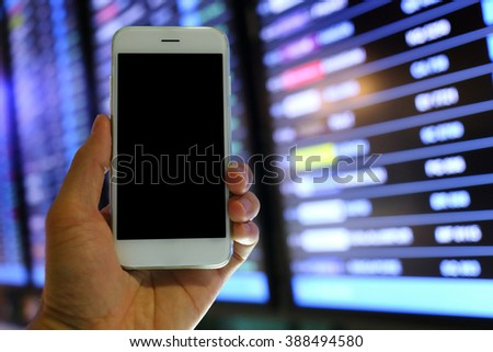 Hand holding smartphone with flight board background - stock photo