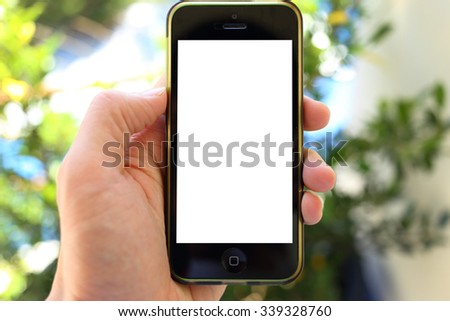 Hand holding smartphone with green leaves background - stock photo