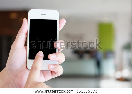 Hand holding smartphone with hotel reception blur background