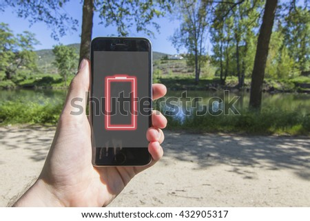 Hand holding smartphone with low battery on the screen in the park. Nature landscape with river, tress and path in the background.