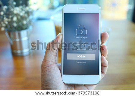Hand holding smartphone with member loging screen on coffee shop background - stock photo