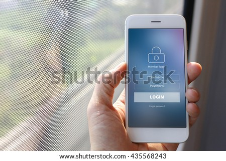 Hand holding smartphone with member loging screen on train window background