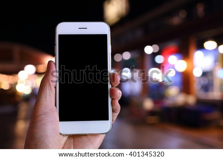 Hand holding smartphone with night background - stock photo