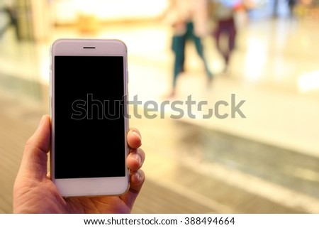 Hand holding smartphone with people background - stock photo