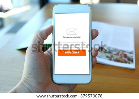 Hand holding smartphone with receive newsletter form on cafe background - stock photo