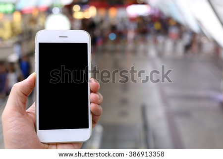 Hand holding smartphone with subway background - stock photo