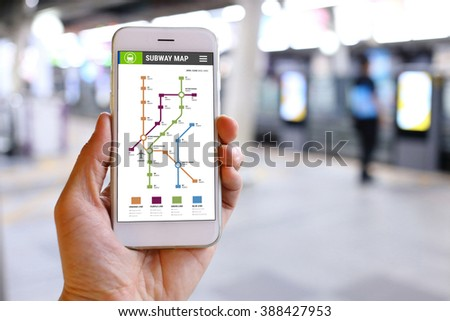 Hand holding smartphone with subway map application background