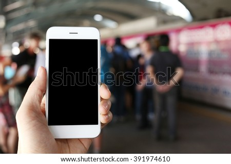 Hand holding smartphone with subway station background - stock photo
