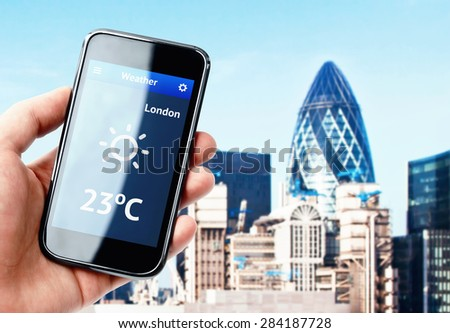 Hand holding smartphone with weather on the screen in London - stock photo