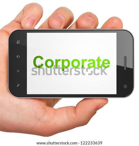 Hand holding smartphone with word Corporate on display. Generic mobile smart phone in hand on white background.