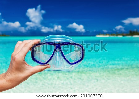 Hand holding snorkel googles against blurred beach and blue sky - stock photo
