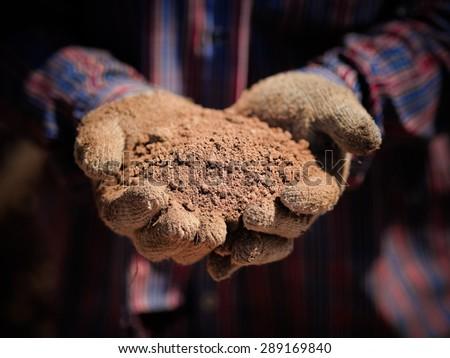 Hand holding soil - stock photo