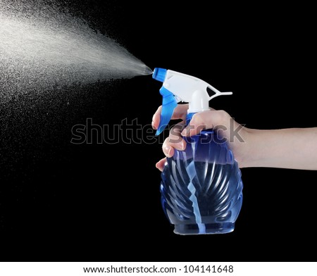 hand holding spray bottle and spraying on black background