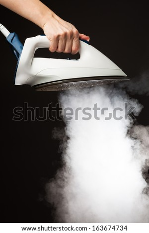 hand holding steam generator iron - stock photo