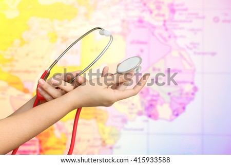 hand holding stethoscope with blur part of world map ,color filter tone background - stock photo