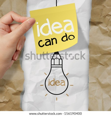 hand holding sticky note with idea can do word  light bulb on crumpled paper as creative concept - stock photo