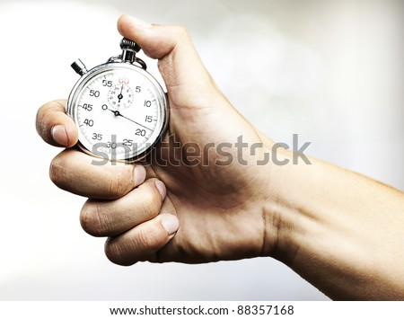 hand holding stopwatch against a abstract background - stock photo