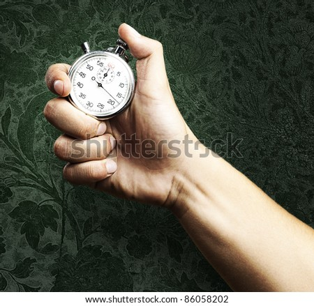 hand holding stopwatch against a grunge background - stock photo