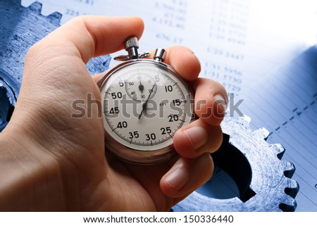 Hand holding stopwatch, budget and two mechanical ratchets