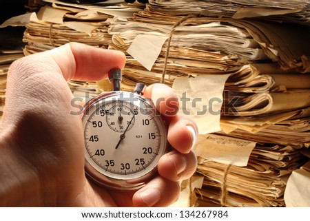 Hand holding stopwatch on document folders background - stock photo