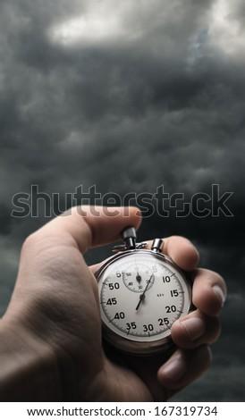 Hand holding stopwatch on stormy sky background - stock photo