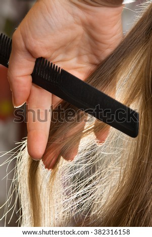 hand holding strand of hair and comb