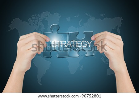 hand holding strategy connected jigsaw puzzle with world map background - stock photo