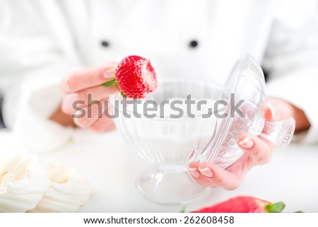 Hand holding strawberry covered in sugar - stock photo