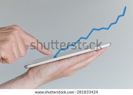 Hand holding tablet. Concept of increasing sales from mobile online shopping. Positive growth chart from use of smartphones / tablets.  - stock photo