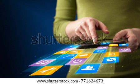 Hand holding tablet device with media application concept on background
