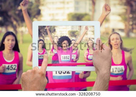 Hand holding tablet pc against cheering young woman winning breast cancer marathon - stock photo