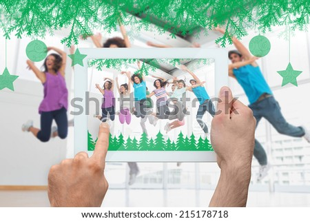 Hand holding tablet pc against fitness class and instructor doing pilates exercise - stock photo