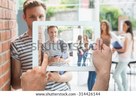 Hand holding tablet pc against handsome student smiling and holding tablet - stock photo