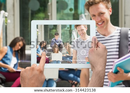 Hand holding tablet pc against handsome student smiling at camera outside - stock photo