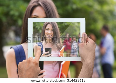 Hand holding tablet pc against pretty student sending a text outside on campus - stock photo