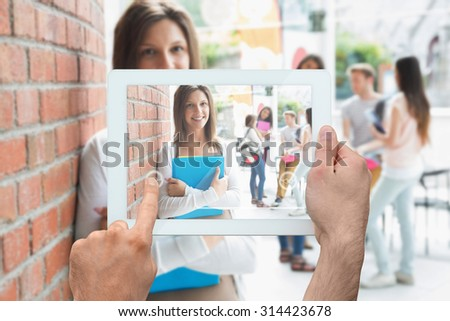 Hand holding tablet pc against pretty student smiling and holding notepads - stock photo