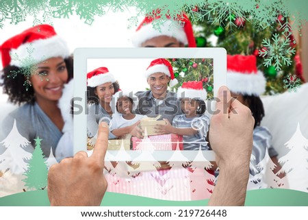 Hand holding tablet pc against snowflakes and fir tree in green - stock photo