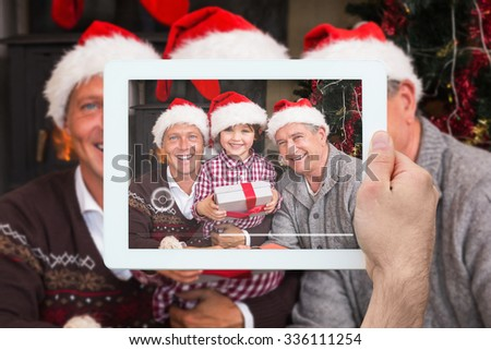Hand holding tablet pc against three generation family celebrating christmas - stock photo