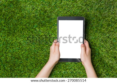 Hand holding tablet pc. over green grass background