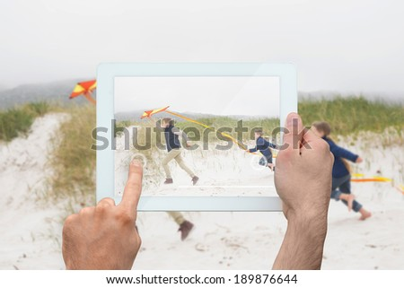 Hand holding tablet pc showing brothers running along beach with kite - stock photo