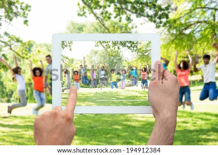 Hand holding tablet pc showing cheerful friends jumping - stock photo