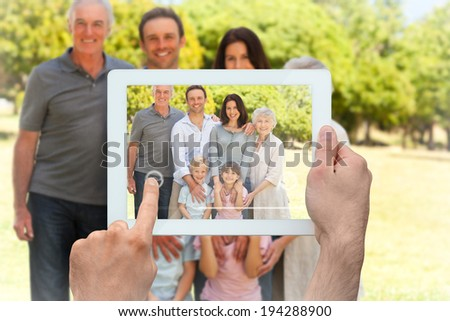 Hand holding tablet pc showing family standing in the park - stock photo